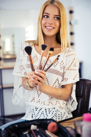 visagist: Happy young visagist woman holding brushes Stock Photo