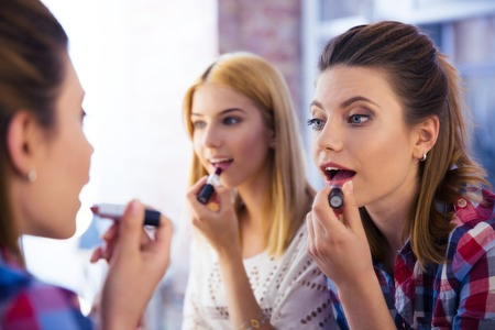 Two young girls looking at mirror and applying lipstick