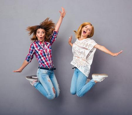 jumping: Dos muchachas alegres que saltan sobre fondo gris