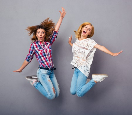 Two cheerful girls jumping over gray background Stok Fotoğraf - 42505922