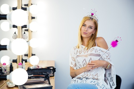 visagist: Cute visagist woman with queen crown and magic wand sitting in beauty salon