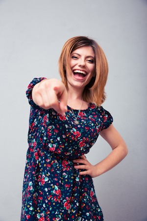 mockery: Laughing woman pointing at camera over gray background