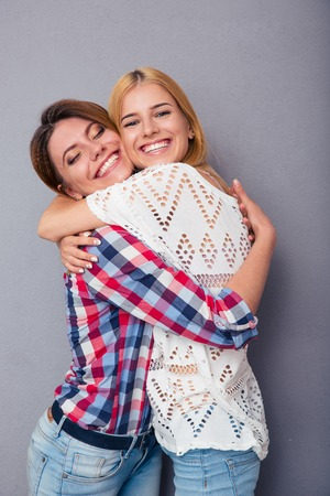 two girls hugging: Happy two girls hugging over gray background Stock Photo