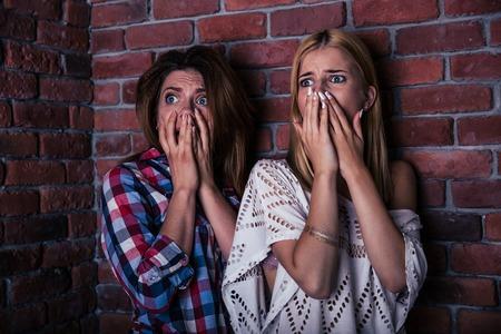 asustado: Dos mujeres scread pie con pared de ladrillo en el fondo Foto de archivo