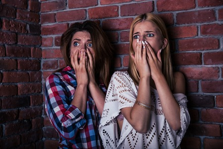 scared: Two scread woman standing with brick wall on background