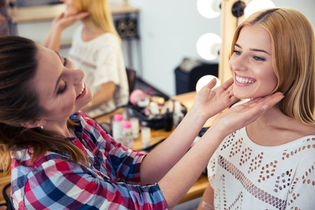 visagist: Happy young visagist looking at woman`s makeup in salon