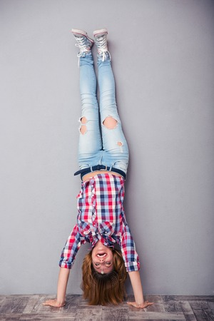 Full length portrait of a woman standing upside down