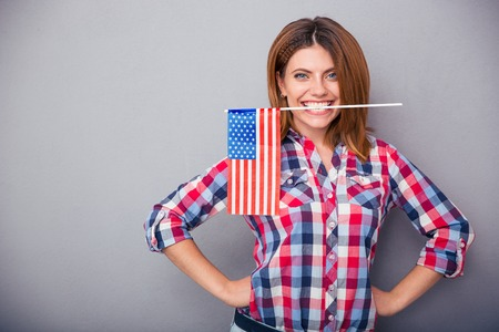 usa flag: Happy young woman holding USA flag in teeth over gray background