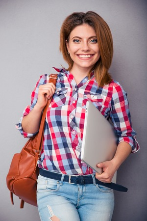 woman holding bag: Happy casual woman holding bag and laptop over gray background