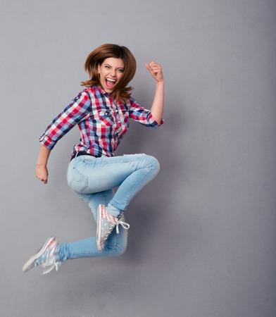 Opgewonden jonge vrouw in casual doek springen over grijze achtergrond Stockfoto