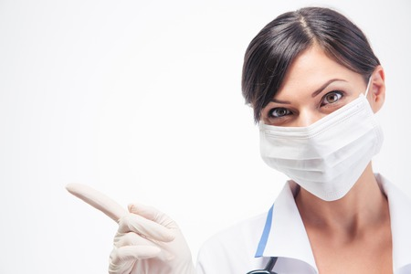 looking away from camera: Portrait of female medical doctor in mask pointing finger away isolated on a white background. Looking at camera Stock Photo