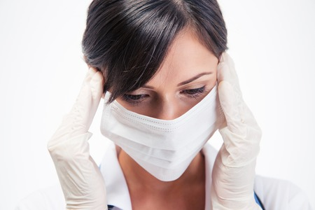 Portrait of a pensive female medical doctor in mask isolated on a white background