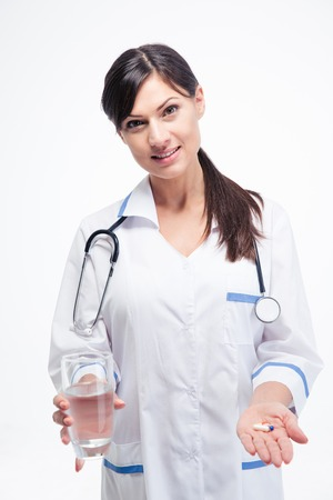 doctor giving glass: Happy female doctor holding medication and glass of water isolated on a white background. Looking at camera