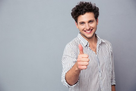 Happy casual man showing thumb up over gray background and looking at camera Stock Photo