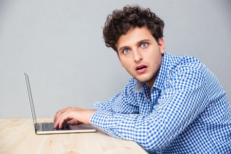 ノート パソコンとテーブルに座って、カメラを見てショックを受けた男の側ビュー肖像
