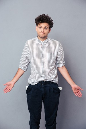 empty: Handsome man shrugging and showing his empty pocket over gray background. Looking at camera