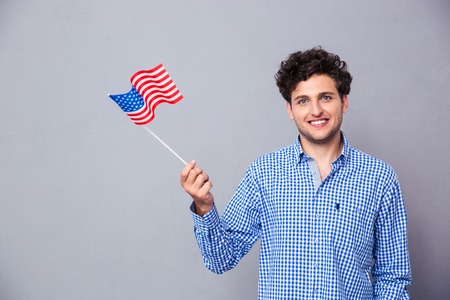 Portrait of a casual smiling man holding USA flag over gray background Stock Photo