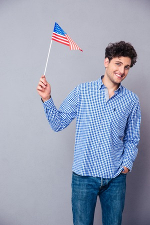 4s: Portrait of a casual happy man holding USA flag over gray background