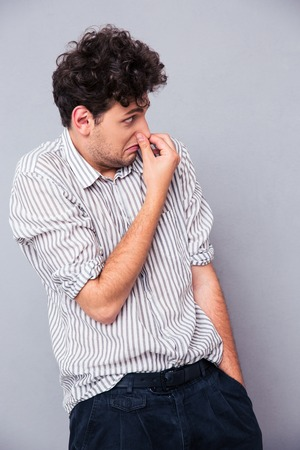 unbearable: Casual man covering his nose with hand over gray background