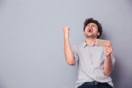 празднование: Счастливый человек держит смартфон и празднует свой успех на сером фоне