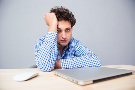 one adult only: Pensive sad man sitting at the table with laptop over gray background Stock Photo