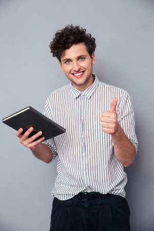 man holding book: Happy young man holding book and showing thumb up over gray background