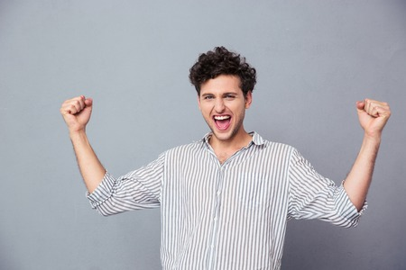 Hombre joven acertado que celebra su ganador sobre fondo gris. Mirando a la cámara