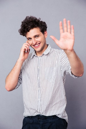 Smiling young man talking on the phone and showing greeting gesture at camera over gray background
