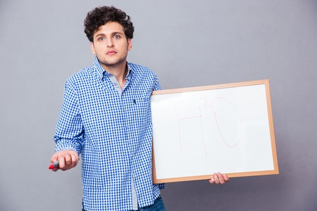 shrugging: Young male student holding text board with marker and shrugging