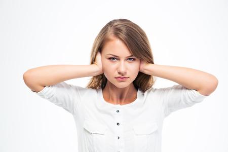 oreja: Mujer hermosa joven que cubre sus oídos aislados en un fondo blanco. Mirando a la cámara