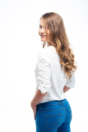 Back view portrait of a happy young woman standing isolated on a white background and looking at camera