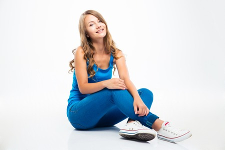 Portrait of a smiling young girl sitting on the floor isolated on a white background