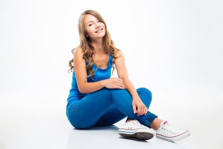 Portret van een lachende jonge meisje zittend op de vloer geïsoleerd op een witte achtergrond