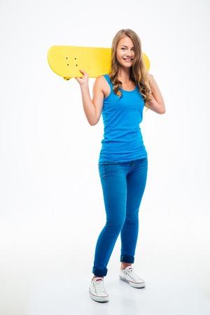 흰색 배경에 고립 된 스케이트 보드를 들고 웃는 어린 소녀의 전체 길이 초상화
