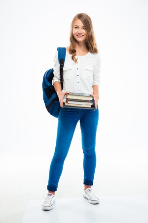 Full length portrait of a young girl with backpack and books standing isolated on a white background. Looking at camera