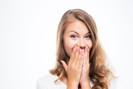 silencio: Retrato de una mujer joven feliz cubriendo su boca aislado en un fondo blanco. Mirando a la cámara