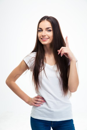 19's: Happy young girl pointing finger up isolated on a white background. Looking at camera