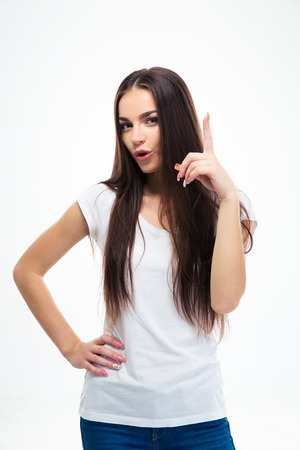 19's: Pretty young woman pointing finger up isolated on a white background. Looking at camera
