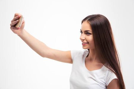 Smiling attractive woman making selfie photo on smartphone isolated on a white background
