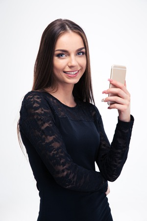 black dress: Happy woman in trendy black dress using smartphone isolated on a white background and looking at camera