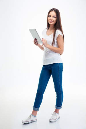Full length portrait of a smiling beautiful woman holding tablet computer isolated on a white background. Looking at camera Stockfoto