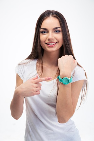 looking at watch: Happy young girl pointing finger at her watch isolated on a white background. Looking at camera