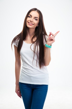 19's: Smiling beautiful woman pointing finger away isolated on a white background