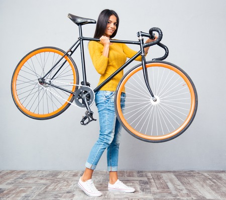bicycle wheel: Smiling young woman holding bicycle on shoulder on gray background. Looking at camera