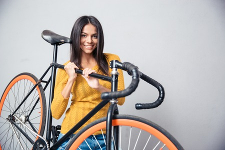 cycler: Smiling cute woman holding bicycle on shoulder on gray background. Looking at camera