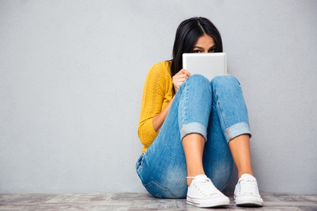 Funny woman sitting on the floor and covering her face with tablet computer on gray abckground
