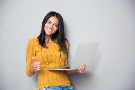 노트북을 들고 회색 배경 위에 엄지 손가락을 게재하는 아름 다운 여자를 웃 고. 카메라를 보면서