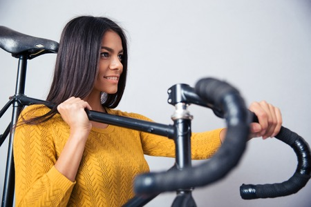 cycler: Happy beautiful woman holding bicycle on shoulder on gray background. Looking away