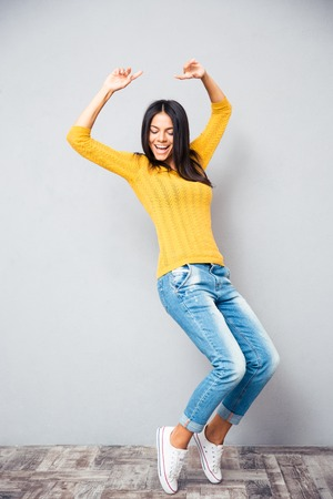 model: Portrait of a happy young woman dancing on gray background