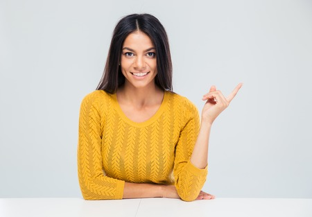 looking away from camera: Smiling young woman sitting at the table and pointing finger away over gray background. Looking at camera Stock Photo